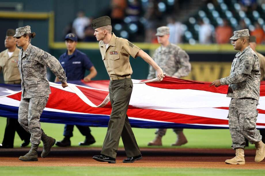 Members of the armed services hold a giant American Flag during pre-game ceremonies.