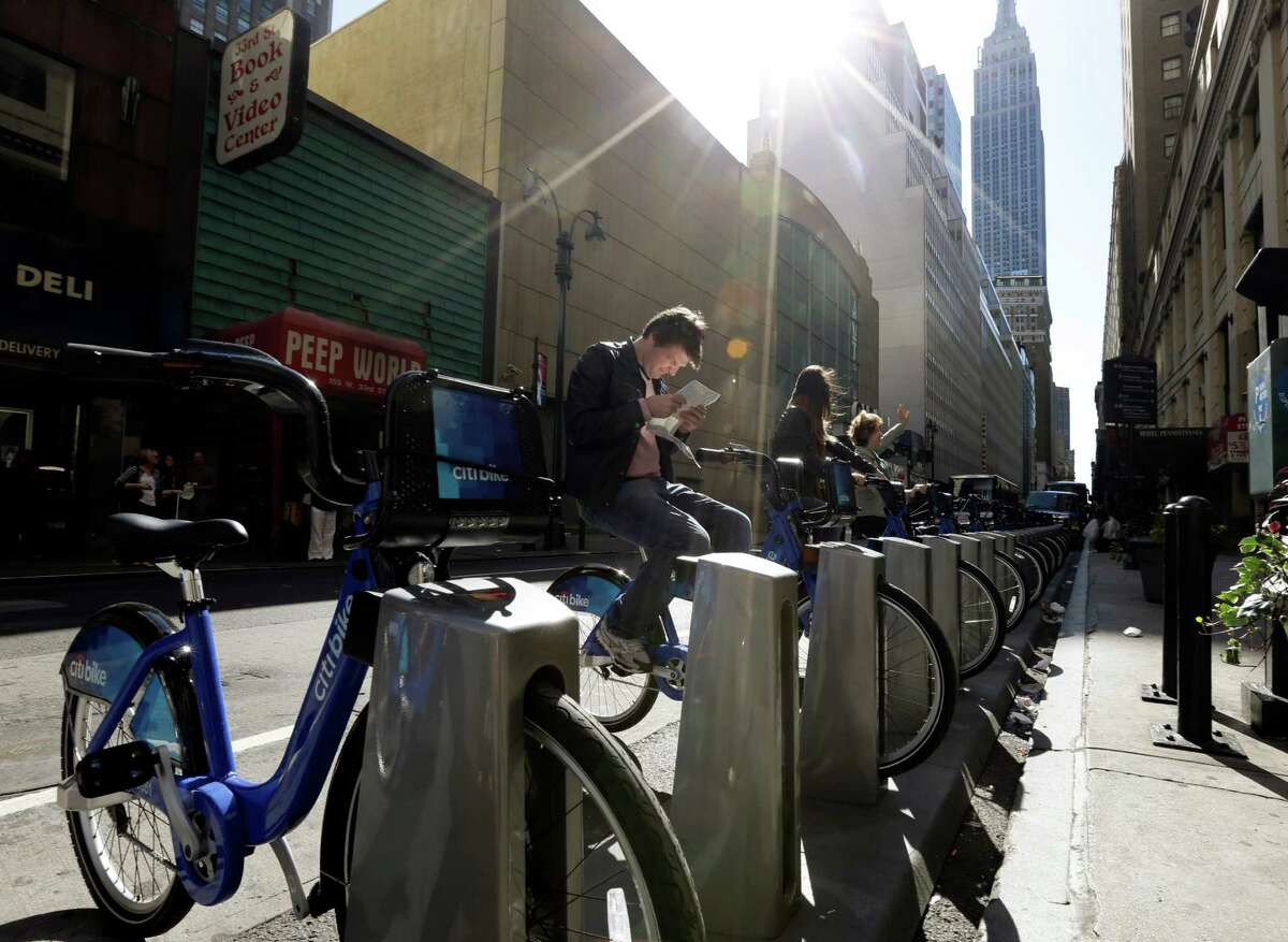 Tourists sit on bikes that are available as part of a bike share program Monday, May 27, 2013, in New York. The privately funded Citi Bike bike-share program will launch with 6,000 bikes at 330 docking stations in Manhattan and parts of Brooklyn. Officials hope to expand to 10,000 bikes and 600 docking stations in Manhattan, Brooklyn and Queens. (AP Photo/Frank Franklin II)