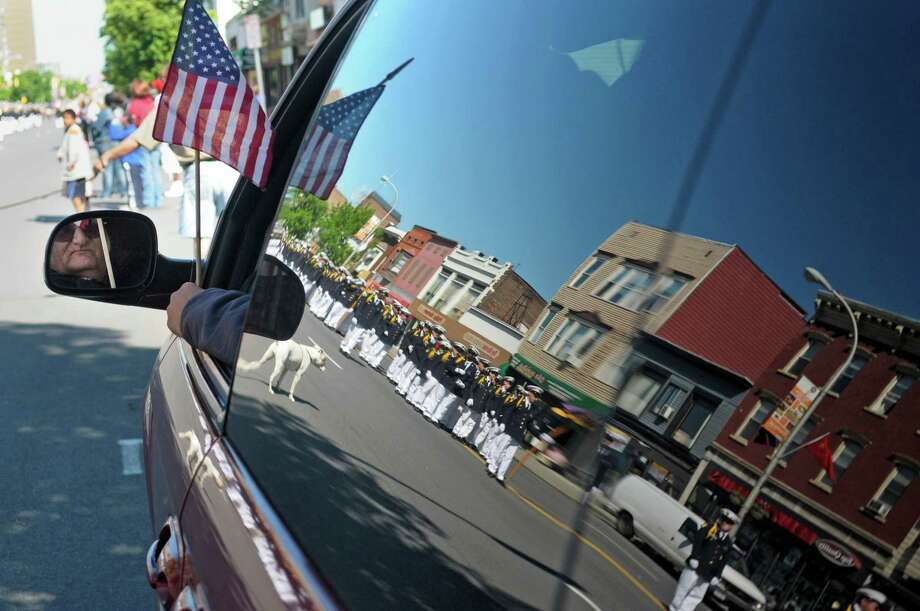 Doug Gibson, of Rensselaer, is reflected in his side mirror as he watches students from Christian Brothers Academy march by during the  Albany Memorial Day Parade on Monday, May 27, 2013 in Albany, NY.   Gibson and his girl friend, Carol Reichel, of Colonie, not pictured, have been coming to the parade for the past 43 years.  (Paul Buckowski / Times Union) Photo: Paul Buckowski