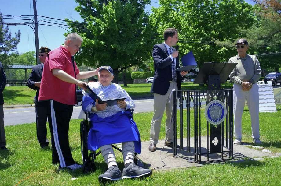 U.S. Rep. Jim Himes, D-Conn., presents medals to World War II veterans James Cappiello, right, and Conrad Angione, left, at the American Legion in Norwalk, Conn. Mr Angione's son, Mike Angione, admres the medals with his father. Andrew Sullivan for The Stamford Advocate Photo: Andrew Sullivan