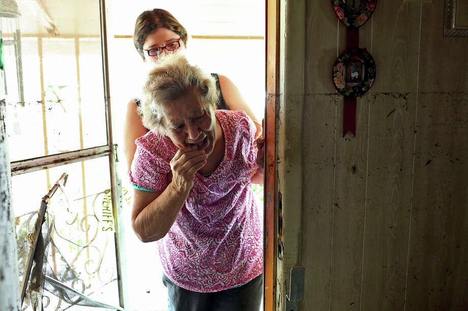 Janey Garza, 87, held by Jamie Vera, sees the damage to her home for the first time since Saturday when floodwater neared the roof of the home she has lived in since 1945 in the neighborhood next to Mission Espada in San Antonio on Monday, May 27, 2013. Garza's home is one of the hardest hit in the neighborhood. Photo: Lisa Krantz, San Antonio Express-News / San Antonio Express-News