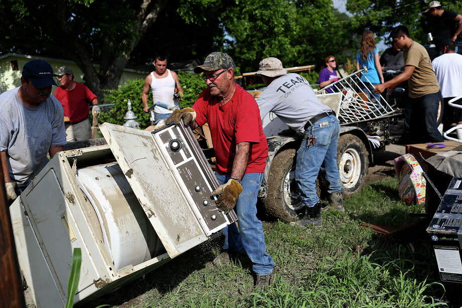 Family and friends of Ian Palacios help with the removal of flooded items from his home as the cleanup from Saturday's flood continues in the neighborhood next to Mission Espada in San Antonio on Monday, May 27, 2013. Photo: Lisa Krantz, San Antonio Express-News / San Antonio Express-News