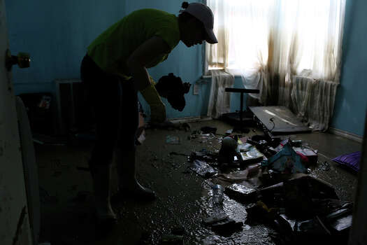 Rhoda R. Council, 22, cleans her flooded room at her home where she lives with her parents in the neighborhood next to Mission Espada in San Antonio on Monday, May 27, 2013. The family has lived there for 20 years and five generations of her family live in the neighborhood. Photo: Lisa Krantz, San Antonio Express-News / San Antonio Express-News