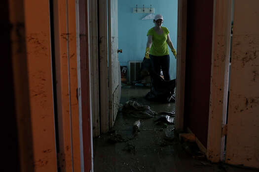 Rhoda R. Council, 22, cleans her flooded room at her home where she lives with her parents in the neighborhood next to Mission Espada in San Antonio on Monday, May 27, 2013. The family has lived there since 1996 and five generations of her family live in the neighborhood. Photo: Lisa Krantz, San Antonio Express-News / San Antonio Express-News