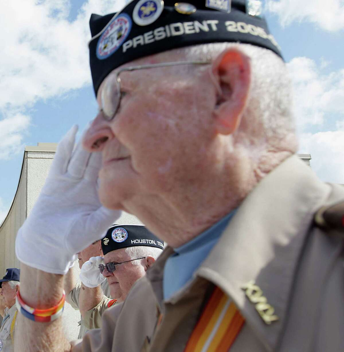 """Veterans Carlos Ballard, left, and Anthony """"Buddy"""" Blair salute on Monday for the presentation of the colors at the Houston National Cemetery."""