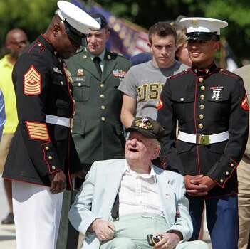Marine Sgt Maj. Ramon Nash, left, speaks with WWII veteran Charles Bannon during the Houston National Cemetery Memorial Day Service. Many former military wore patches and hats displaying their unit names. Photo: James Nielsen, Staff / © 2013  Houston Chronicle