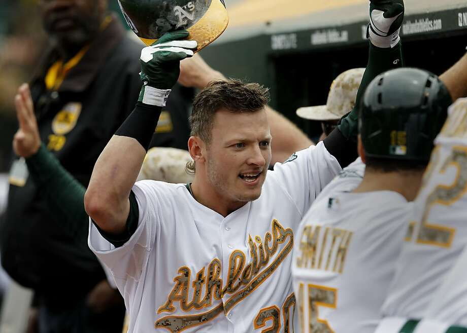 Josh Donaldson is congratulated in the A's dugout after his two-run homer in the fourth inning put Oakland ahead to stay. Photo: Brant Ward, The Chronicle