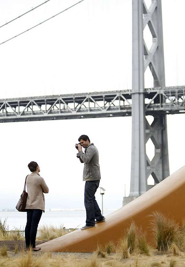 "Michael Barrientos photographs Kristine Braun by the ""Cupid's Span"" sculpture on the Embarcadero. Photo: Carlos Avila Gonzalez, The Chronicle"