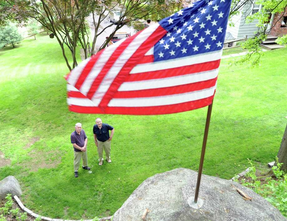 """At right, John Kriskey, 77, a former Army corporal and his friend, James """"Mitch"""" Mitchell, 81, of Port Chester, N.Y., a former Marine corporal who served in the Korean War, below the American Flag that Mitchell placed in a boulder on the """"high ground"""" at Kriskey's Glenville home, Wednesday, May 22, 2013. Photo: Bob Luckey / Greenwich Time"""