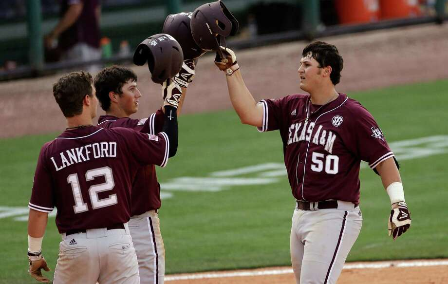 Texas A&M's Hunter Melton (50) is congratulated by teammates after hitting a three-run home run off of Florida's Johnny Magliozzi in their Southeastern Conference tournament college baseball game at the Hoover Met in Hoover, Ala., Tuesday, May 21, 2013. At left is Texas A&M's Cole Lankford (12). (AP Photo/Dave Martin) Photo: Dave Martin, Associated Press / AP