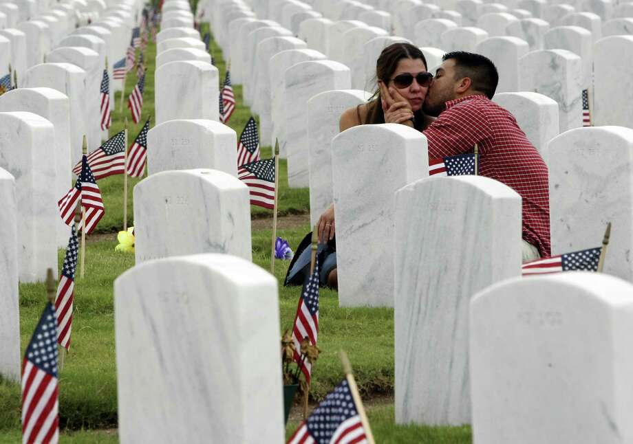 Cyndi Ball and Jesse Garza visit Ball's father's grave after the Memorial Day ceremony at Fort Sam Houston National Cemetery. Photo: Helen L. Montoya / San Antonio Express-News