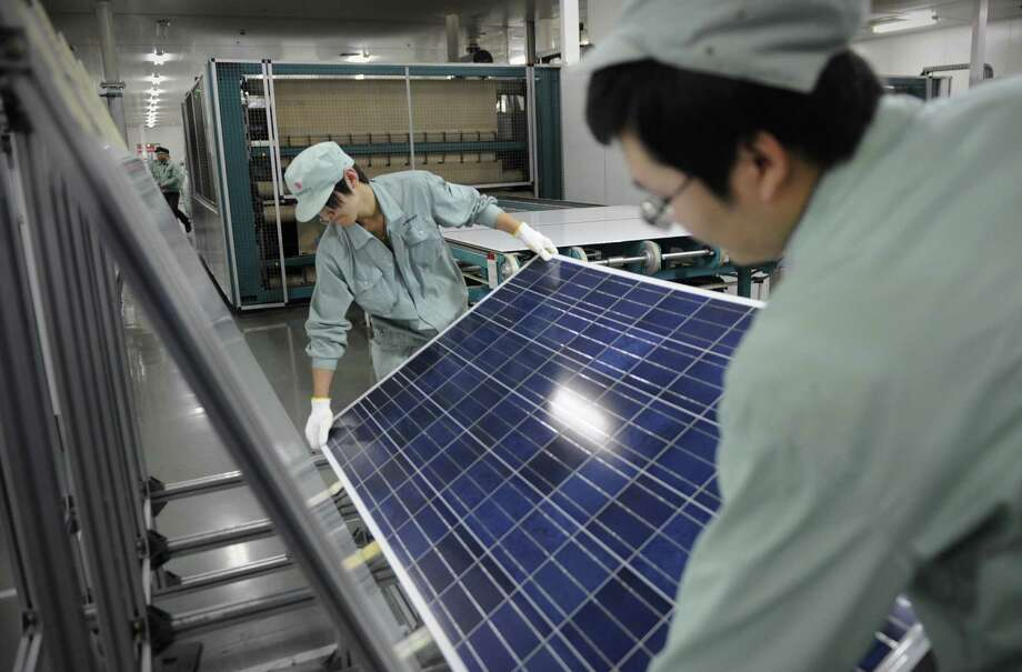 Workers assemble solar panels at a factory of Chinese company Suntech in Wuxi. Europe and China are arguing over tariffs on Chinese-made panels. Photo: PETER PARKS, Staff / AFP