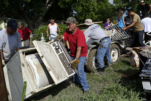 Eloy Martinez (center) is among the helpers removing flooded items from a home in the neighborhood next to the mission. Red Cross Disaster Services can be reached at 210-224-5151. Photo: Lisa Krantz / San Antonio Express-News