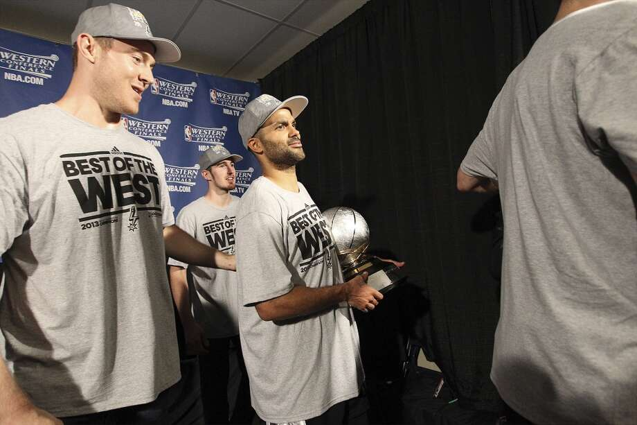 Tony Parker holds the 2013 Western Conference Championship trophy accompanied by teammates Aron Baynes (left) and Nando De Colo as the San Antonio Spurs defeated the Memphis Grizzlies in four games to take move in the NBA Finals at the FedEx Forum in Memphis on Monday, May 27, 2013. (Kin Man Hui/San Antonio Express-News)