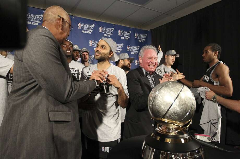 Spurs legend George Gervin (left) congratulates Tony Parker (center) as the Spurs and owner Peter Holt are presented the 2013 Western Conference Championship trophy after defeating the Memphis Grizzlies in four games to move into the NBA Finals at the FedEx Forum in Memphis on Monday, May 27, 2013. (Kin Man Hui/San Antonio Express-News)