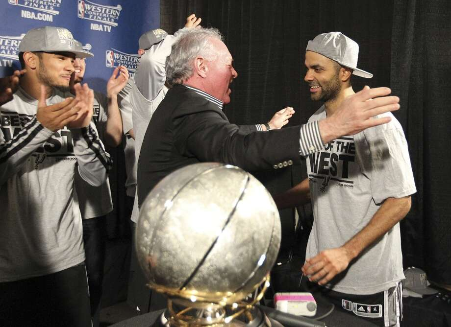 Spurs owner Peter Holt goes to hug Tony Parker as the San Antonio Spurs are presented the 2013 Western Conference Championship trophy after defeating the Memphis Grizzlies in four games at the FedEx Forum in Memphis on Monday, May 27, 2013. (Kin Man Hui/San Antonio Express-News)