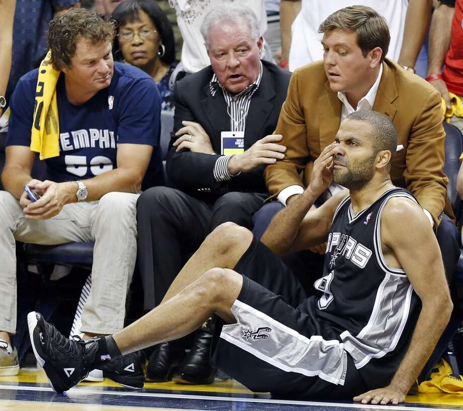 San Antonio Spurs' Tony Parker sits on the court after being hit by Memphis Grizzlies' Marc Gasol during second half action Game 4 of the 2013 Western Conference finals as Spurs owner Peter Holt and his son Peter J. Holt look on Monday May 27, 2013 at the FedEx Forum in Memphis, Tenn. The Spurs won 93-86.