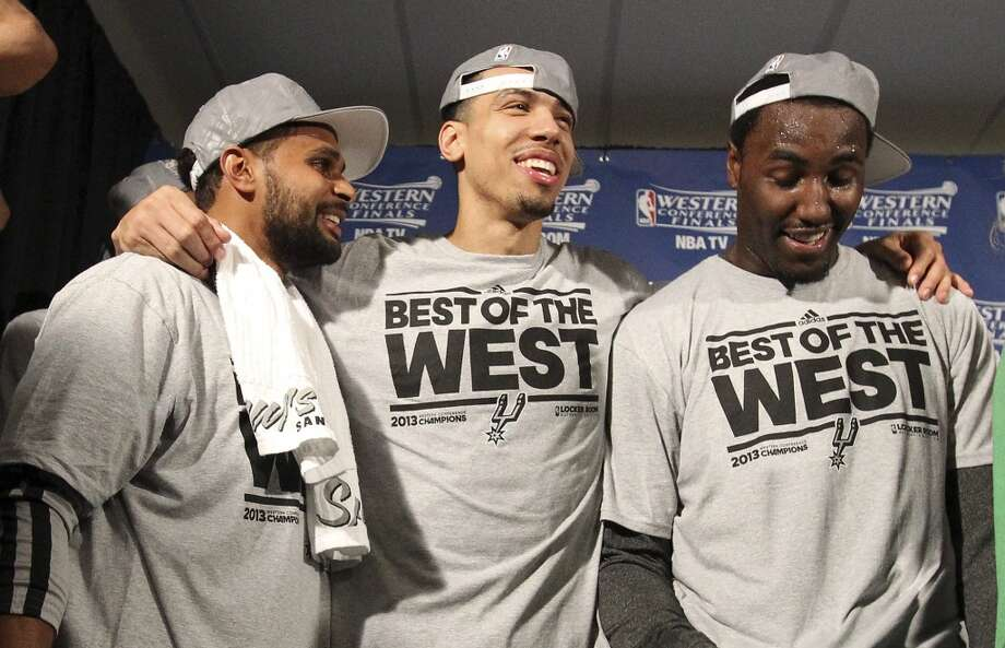 Patty Mills (left), Danny Green and DeJuan Blair savor the moment after the San Antonio Spurs are presented the 2013 Western Conference Championship trophy after defeating the Memphis Grizzlies in four games at the FedEx Forum in Memphis on Monday, May 27, 2013. (Kin Man Hui/San Antonio Express-News)
