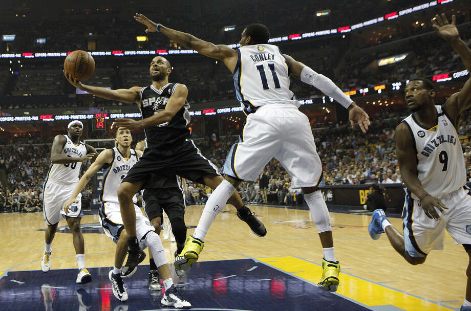 Spurs guard Tony Parker, who made 15 of 21 shots and finished with 37 points and six assists, races into the lane against Grizzlies guard Mike Conley. Photo: Kin Man Hui / San Antonio Express-News
