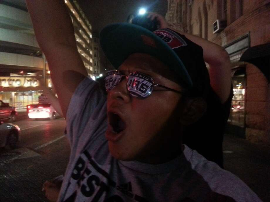 Sam Arce, 21, decked out in Spurs gear, yells to fans as they drive by. Photo by Michelle Mondo.