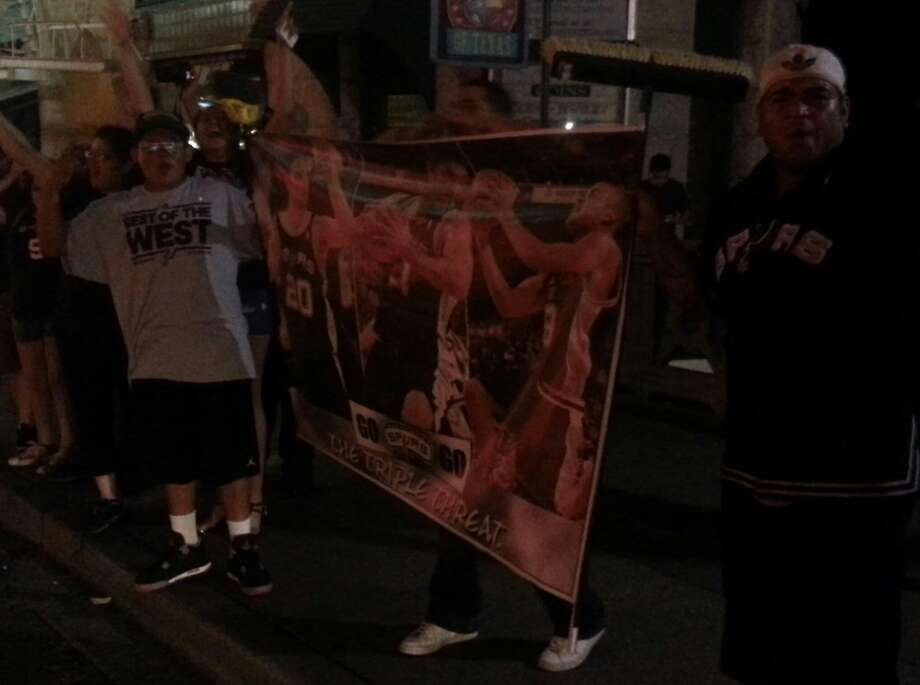 Sam Arce (left) and Sam Leija (right) hold a banner taped to brooms. The makeshift memorabilia was popular among those passing by. Photo by Michelle Mondo.