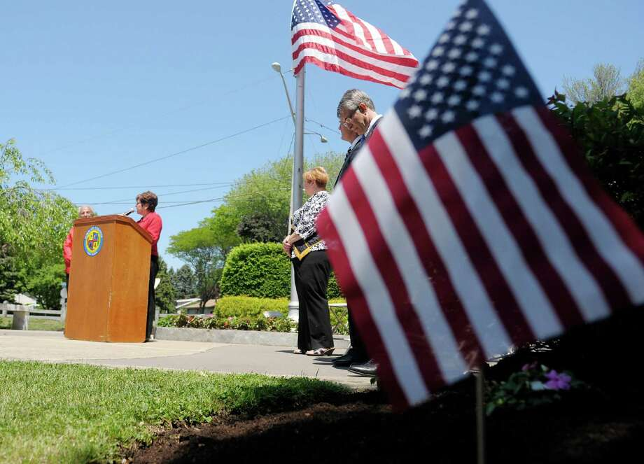 Colonie Town Supervisor Paula Mahan, background left, addresses those gathered at West Albany Memorial Park during the 14th annual wreath laying ceremony put on by the Italian Benevolent Society and Ladies Auxiliary on Monday, May 27, 2013 in Albany, NY.   (Paul Buckowski / Times Union) Photo: Paul Buckowski