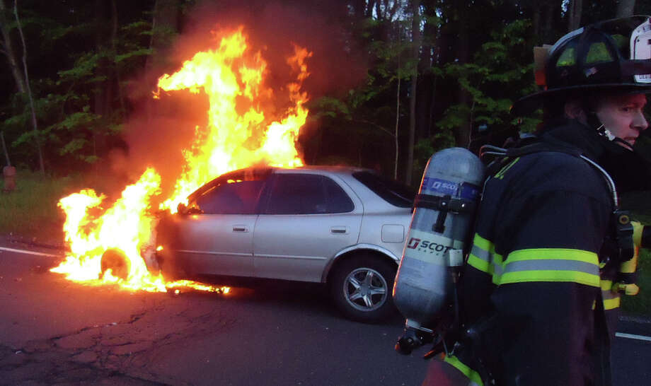 Firefighters from Westport and Norwalk battled a car fire on the Merritt Parkway, near northbound Exit 40, that shut down holiday traffic Monday night. Photo: Norwalk Fire Department / Westport News contributed
