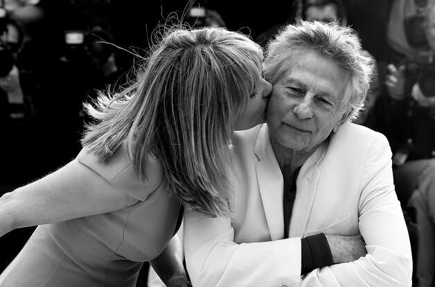 "French actress Emmanuelle Seigner (L) kisses on May 25, 2013 her husband, director Roman Polanski during a photocall for the film ""Venus in Fur"" presented in Competition at the 66th edition of the Cannes Film Festival in Cannes. Cannes, one of the world's top film festivals, opened on May 15 and will climax on May 26 with awards selected by a jury headed this year by Hollywood legend Steven Spielberg. Photo: VALERY HACHE, AFP/Getty Images / 2013 AFP"