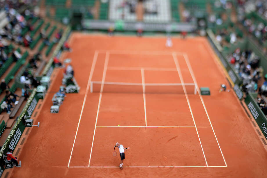 A picture taken with a tilt and shift lens shows Australia's Lleyton Hewitt (down) serving to France's Gilles Simon during their French Tennis Open first round match at the Roland Garros stadium in Paris, on May 26,  2013. Photo: MARTIN BUREAU, AFP/Getty Images / 2013 AFP