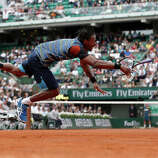 France's Gael Monfils dives in a try to return to Czech Republic's Tomas Berdych during their French Tennis Open first round match at the Roland Garros stadium in Paris, on May 27,  2013.