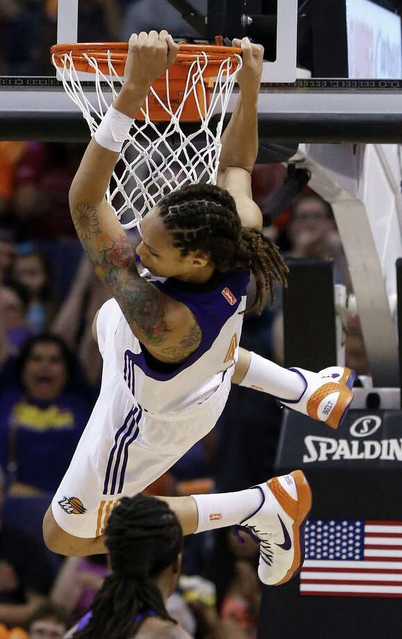 Phoenix Mercury's Brittney Griner hangs on the rim after making a two-handed dunk against the Chicago Sky in the second half during a WNBA basketball game on Monday, May 27, 2013, in Phoenix. The Sky defeated the Mercury 102-80. (AP Photo/Ross D. Franklin) Photo: Ross D. Franklin, Associated Press / AP
