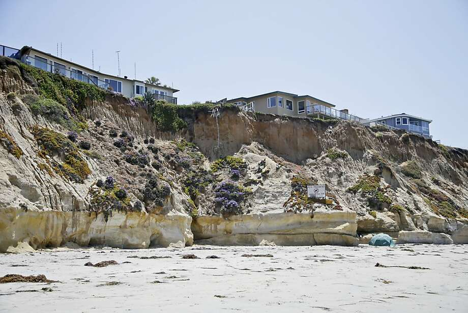 Homes hang over the edge of a cliff in Solana Beach, where the base of the cliff lacks a seawall. Photo: Lenny Ignelzi, Associated Press
