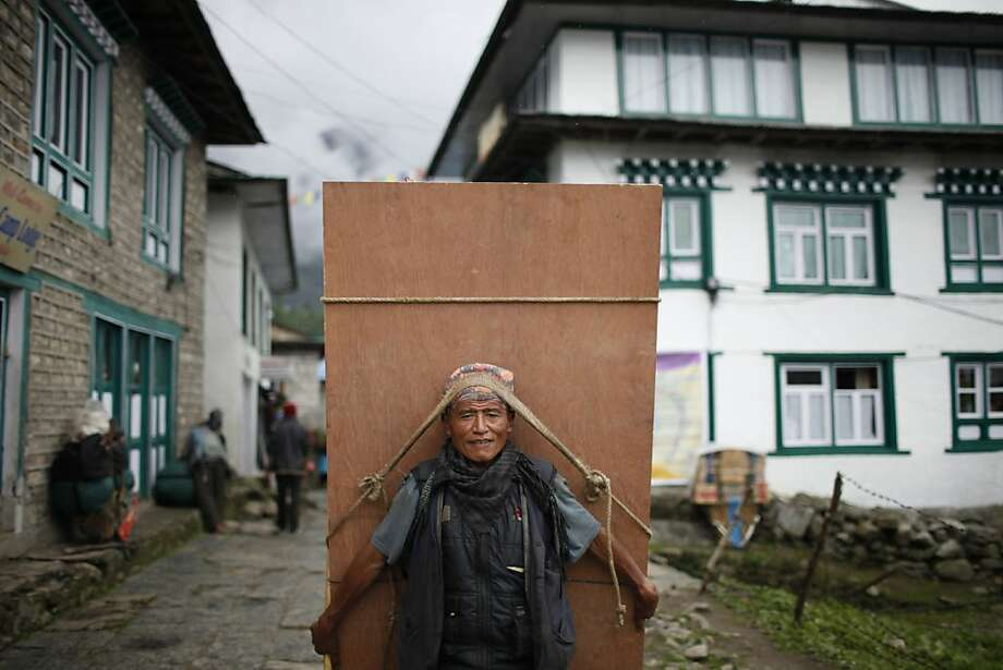 All our sherpas are board-certified:A laborer carries a sheet of plywood in   Lukla, Nepal, a popular landing spot for trekkers visiting the Himalayas. Photo: Niranjan Shrestha, Associated Press