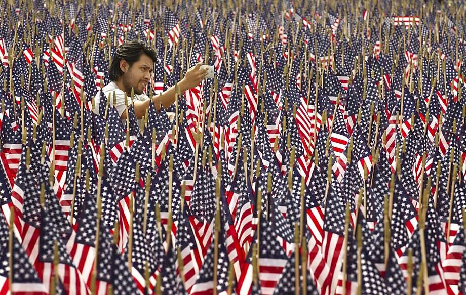 Waving in remembrance:Edgar Yepez takes a photo amid 7,000 American flags on   display for Memorial Day outside the Long Center in Austin, Texas. The flags honor   fallen veterans of the wars in Iraq and Afghanistan. Photo: Jay Janner, Associated Press