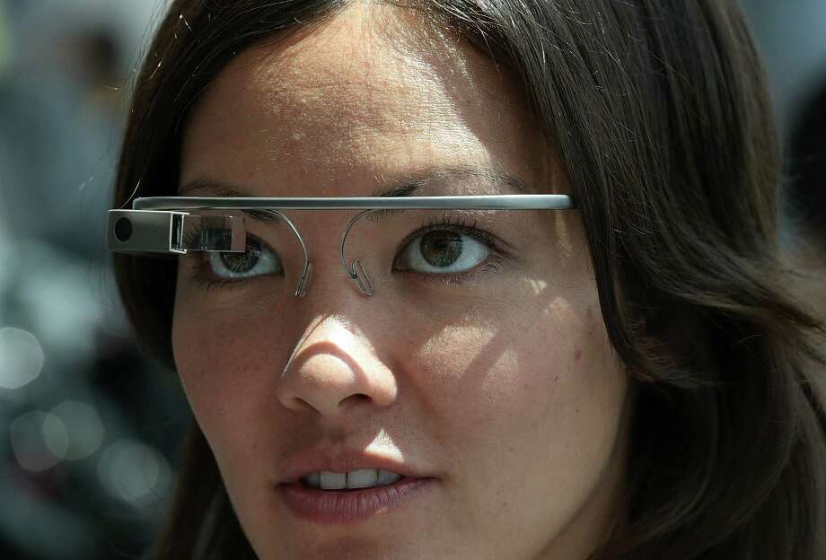 A woman tries on a Google Glass at a conference in San Francisco earlier this month. The device can take still photos and video, plus project maps and other data that only the wearer can see. Photo: Justin Sullivan, Getty Images / 2013 Getty Images