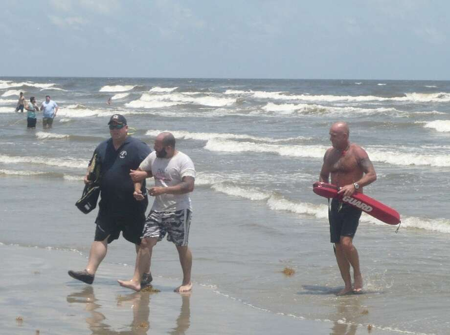 Jacob Grant is brought ashore by Jamaica Beach firefighter, left, and Beach Patrol Chief Peter Davis. (www.ThePoliceNews.net)