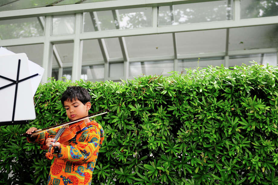 Arya Hino, 6, who has been practicing for 1 1/2 years, plays his violin during Folklife to work on his confidence on Monday, May 27, 2013 at Seattle Center. The soggy Memorial Day weather brought out fewer crowds than previous days, but was still attended by thousands. (Photo by Lindsey Wasson) Photo: LINDSEY WASSON, SEATTLEPI.COM / SEATTLEPI.COM