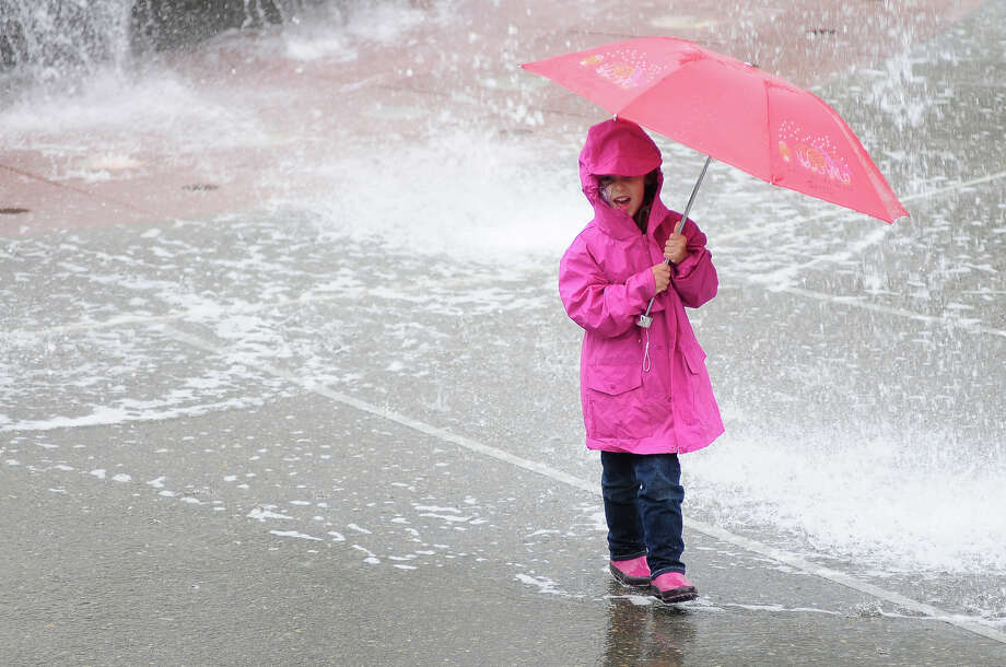 A young girl makes a face as rain and streams of water from the International Fountain fall on her umbrella during Folklife on Monday, May 27, 2013 at Seattle Center. The soggy Memorial Day weather brought out fewer crowds than previous days, but was still attended by thousands. (Photo by Lindsey Wasson) Photo: LINDSEY WASSON, SEATTLEPI.COM / SEATTLEPI.COM