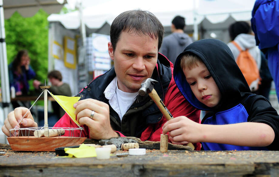 Paul Van Metre and his son Dane, 7, work together to build a wooden boat during Folklife on Monday, May 27, 2013 at Seattle Center. The soggy Memorial Day weather brought out fewer crowds than previous days, but was still attended by thousands. (Photo by Lindsey Wasson) Photo: LINDSEY WASSON, SEATTLEPI.COM / SEATTLEPI.COM