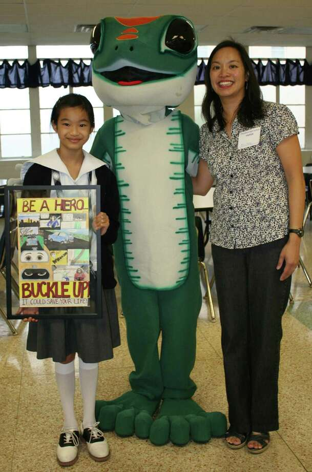 "GEICO Insurance recently announced Providence Catholic School sixth-grader Elisabeth Wang, a Stone Oak-area student, was one of 15 winners nationwide of its annual safety poster contest. Wang's poster, ""Be a hero — Buckle up,"" was chosen from more than 600 elementary- and middle-school student submissions to the contest. Wang received a $250 check from GEICO representative Jay Vaden (not pictured) and the GEICO Gecko at a school assembly as her mother Aline Wang, right, looked on. Photo: Courtesy Photo"