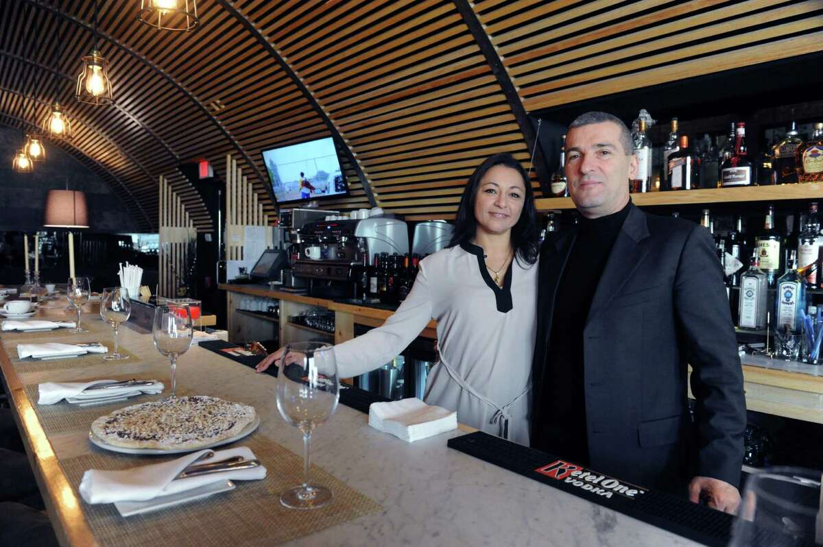 Silvy and Claudio Ridolfi, the owners of Cotto Wine Bar Pizzeria, stand at the bar of their new Italian restaurant in Stamford, Conn.