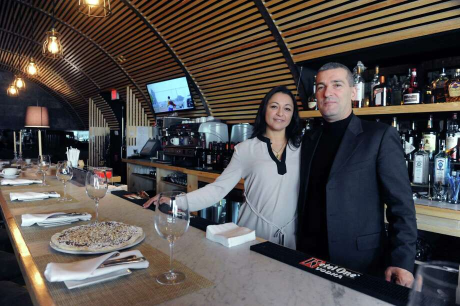 Silvy and Claudio Ridolfi, the owners of Cotto Wine Bar Pizzeria, stand at the bar of their new Italian restaurant in Stamford, Conn. Photo: Helen Neafsey / Greenwich Time
