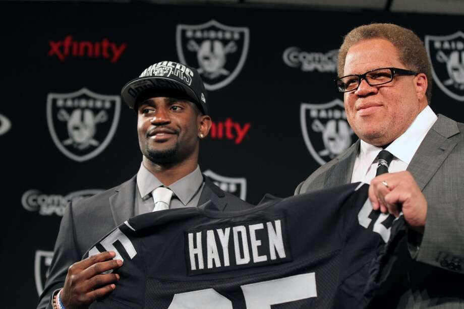 Oakland Raiders first round draft pick D.J. Hayden, left, a cornerback from Houston, holds his jersey with general manager Reggie McKenzie at a news conference at the team's training facility in Alameda, Calif., Friday, April 26, 2013.