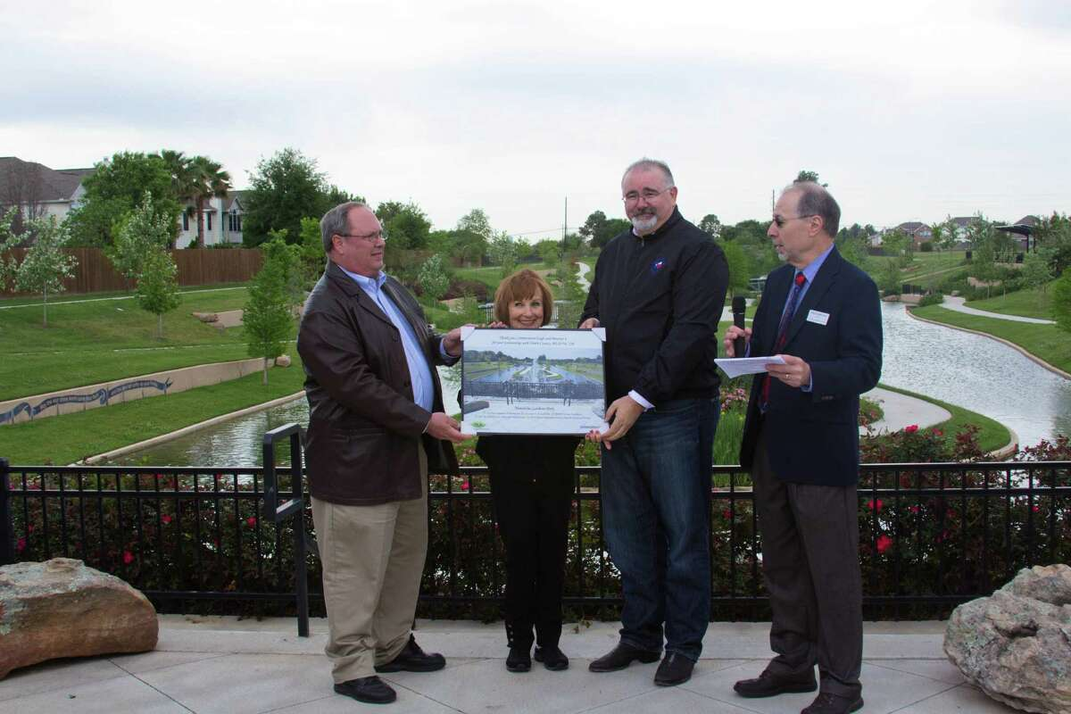 Harris County MUD 230 board members Luke Grainge, left, Kathryn Wright and Paul Raschke, right, presented a print of Mandolin Gardens Park to Precinct 4 Commissioner Jack Cagle during a recognition ceremony at the park.