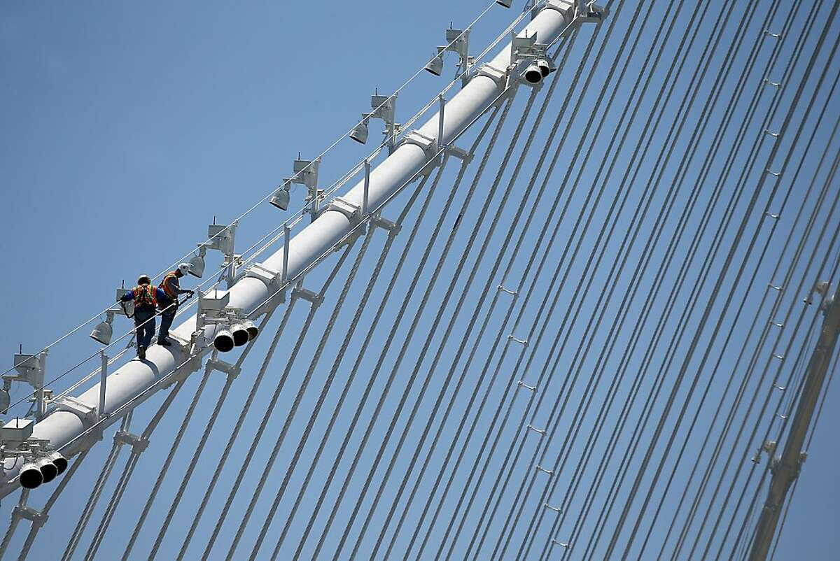 OAKLAND, CA - MAY 23: Workers walk on a cable of the newly constructed eastern span of the San Francisco-Oakland Bay Bridge on May 23, 2013 in Oakland, California. Bridge workers began installing large steel saddles over two seismic safety devices on the new East Span of the San Francisco-Oakland Bay Bridge to fix a problem with broken bolts on two shear keys. The bridge has been under construction since 2002 with an estimated price tag of $6.3 billion and will have the world's tallest Self-Anchored Suspension (SAS) tower once completed. (Photo by Justin Sullivan/Getty Images)