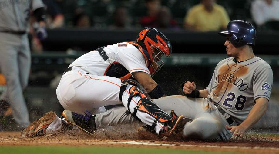 Astros catcher Carlos Corporan (22) tags out Rockies third baseman Nolan Arenado in a double play to end the third inning.