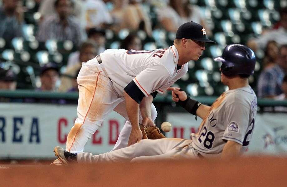Rockies third baseman Nolan Arenado slides into third base as Astros third baseman Matt Dominguez tries to make a play during the third inning.
