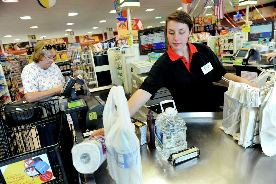 Cashier Haley Votra, right, bags groceries for a customer on Tuesday, May 28, 2013, at Tops market in Hoosick Falls, N.Y. (Cindy Schultz / Times Union) Photo: Cindy Schultz / 00022593A