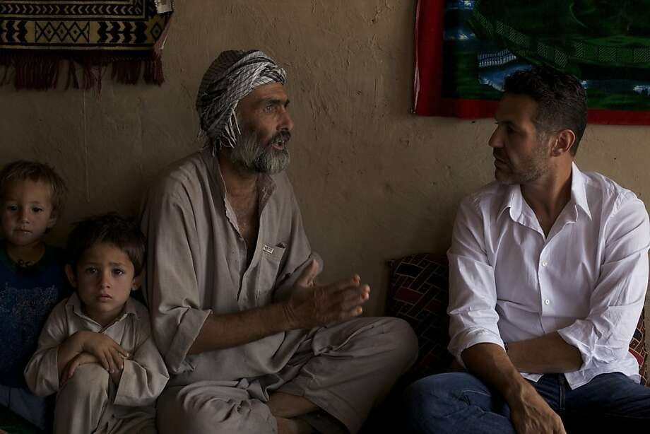 Khaled Hosseini (right), who started a foundation, listens to the issues of Afghans while serving as a U.S. goodwill envoy. Photo: Tim Page, UNHCR