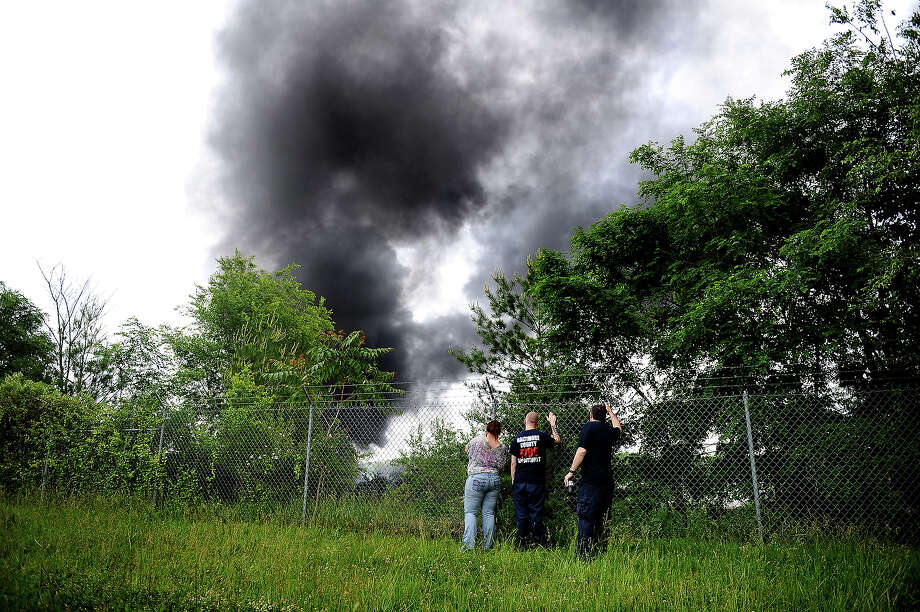 As smoke fills the sky, passersby try to get a better look of a train derailment that caused a major explosion in the Rosedale neighborhood on May 28, 2013 in Baltimore, Maryland. Residents in nearby neighborhoods were advised to voluntarily evacuate. Photo: Patrick Smith, Getty Images / 2013 Getty Images